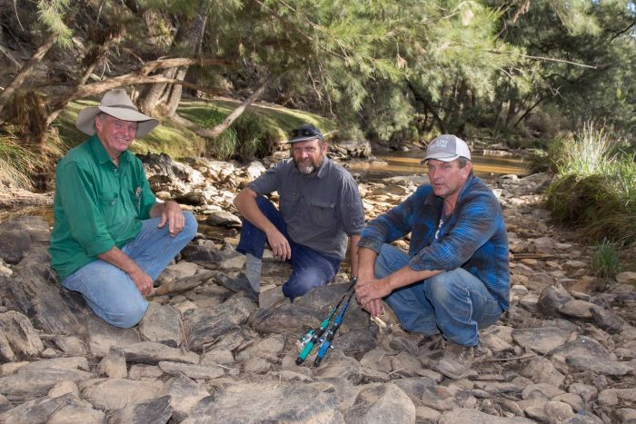 Three men with some fishing rods sit on rocks in front of a river